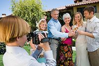 Boy recording family on camcorder while raising toast in garden
