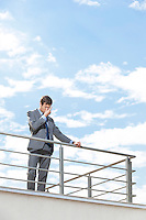 Stressed young businessman rubbing eyes on terrace against sky