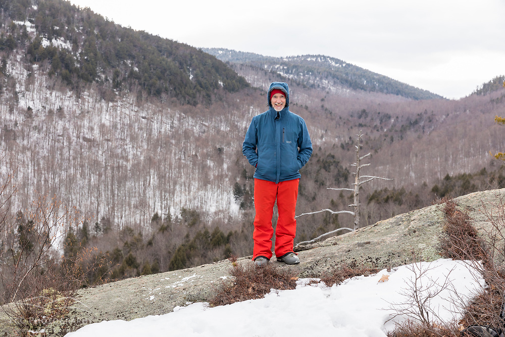A man takes a break while hiking on the ledges of Huckleberry Mountain in South Johnsburg, New York. Adirondack Mountains.