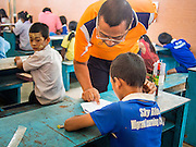 06 MARCH 2014 - MAE SOT, TAK, THAILAND: A teacher works with students at the Sky Blue School. There are approximately 140 students in the Sky Blue School, north of Mae Sot. The school is next to the main landfill for Mae Sot and serves the children of the people who work in the landfill. The school relies on grants and donations from Non Governmental Organizations (NGOs). Reforms in Myanmar have alllowed NGOs to operate in Myanmar, as a result many NGOs are shifting resources to operations in Myanmar, leaving Burmese migrants and refugees in Thailand vulnerable. The Sky Blue School was not able to pay its teachers for three months during the current school year because money promised by a NGO wasn't delivered when the NGO started to support schools in Burma. The school got an emergency grant from the Burma Migrant Teachers' Association and has since been able to pay the teachers.      PHOTO BY JACK KURTZ
