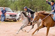 """09 SEPTEMBER 2007 -- ST. MICHAELS, AZ: Racers KYLE BEGAY (left) on Cody and JONAH BEGAY on Therapist come into the finish line at the end of a two and a half mile long race at a traditional Navajo Horse Race in the summit area of the Navajo Indian reservation about 10 miles west of St. Michaels, AZ. Traditional horse racing is making a comeback on the Navajo reservation. The races are run on improvised courses that vary depending on the local terrain. Use of saddles is optional (except in the """"Cowhand Race"""" which requires a western style saddle) and many jockeys ride bareback. The distances vary from one mile to as long as thirty miles. Traditional horse races were common until the 1950's when they fell out of favor, but there has been a resurgence in traditional racing since the late 1990's and now there is a traditional horse racing circuit on the reservation. The race was organized by the Begay family of Steamboat, AZ and run on private land about three miles from a paved road. Jonah Begay won the race. Photo by Jack Kurtz"""