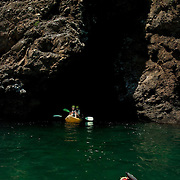 Kayakers exiting one of the many volcanic sea caves that honeycomb the shoreline of Santa Cruz Island, Channel Islands National Park, CA.
