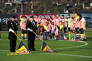 The Exeter players stand around the centre circle as the standards are lowered for a 2 minutes silence to mark remembrance day during the EFL Sky Bet League 2 match between Exeter City and Cheltenham Town at St James' Park, Exeter, England on 16 November 2019.