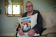 Margaret Lewis, pictured at her home in Kirkby, Liverpool. Mrs Lewis faces the prospect of having to pay additional money for rent with the introduction of the so-called Bedroom Tax, which comes into effect in April 2013. She lost her son Carl, then 18 (pictured on the cushion) at the Hillsborough football stadium disaster in 1989 and may have to move to a smaller property than the one in which she brought up her son. The street which she lives was renamed in Carl's honour around 15 years ago.