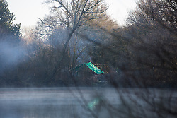 Harefield, UK. 19 January, 2020. A view through early morning mist over a lake in Colne Valley Regional Park towards the Colne Valley wildlife protection camp from which bailiffs acting for HS2 have been evicting activists from Save the Colne Valley and Stop HS2.
