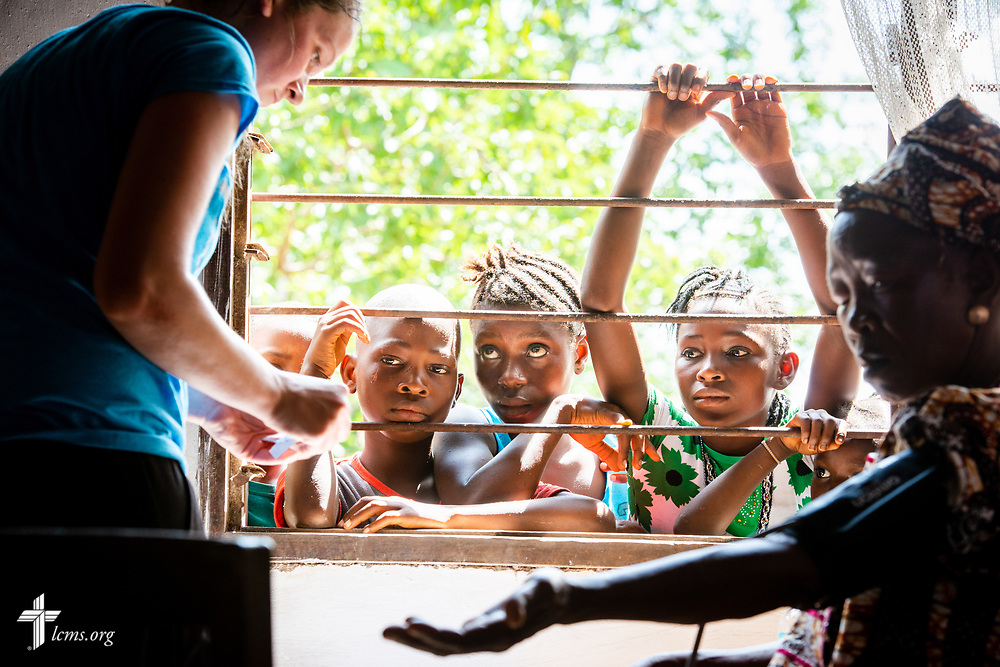Teenagers watch as Hayden Rensner, a student at Concordia University, Nebraska, collects vitals from a patient on the first day of the LCMS Mercy Medical Team on Monday, May 7, 2018, in the Yardu village outside Koidu, Sierra Leone, West Africa. LCMS Communications/Erik M. Lunsford