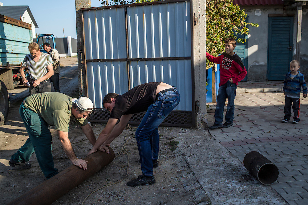 A group of internally displaced people who fled the besieged city of Donetsk unload a large pipe needed to install a heating system for the small seaside resort that has become their home on Tuesday, October 14, 2014 in Berdyansk, Ukraine. Photo by Brendan Hoffman, Freelance