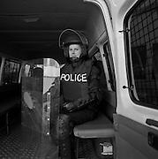 Polizistin mit Helm und Schild im Bus, policière avec casque et bouclier anti-manif, policewoman in bus with shield. © Romano P. Riedo