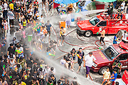 14 APRIL 2013 - BANGKOK, THAILAND:  Bangkok firefighters hose down the crowd in a community water fight on April 14, 2013 in Bangkok, Thailand. The Songkran festival is celebrated in Thailand as the traditional New Year's Day from 13 to 15 April. The throwing of water originated as a way to pay respect to people and is meant as a symbol of washing all of the bad away. PHOTO BY JACK KURTZ