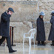 People are seen on the plaza near The Kotel as snow and rain fall at The Western Wall on January 7, 2015 in Jerusalem, Israel. (Photo by Elan Kawesch)