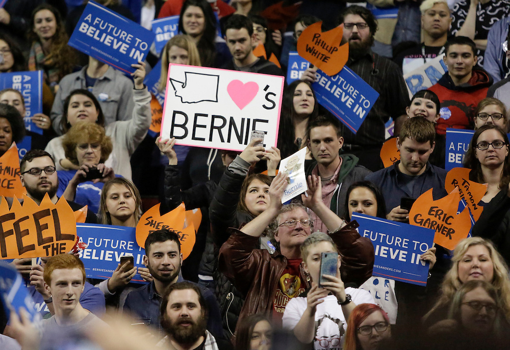 A supporter holds a sign with the Washington state on it during a rally for Democratic presidential candidate Bernie Sanders at Key Arena on March 20, 2016 in Seattle.  AFP PHOTO/JASON REDMOND