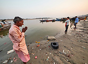 India, Uttar Pradesh. Varanasi (Benares). A Hindu pilgrim praying at Raj Ghat at the holy Ganges river.