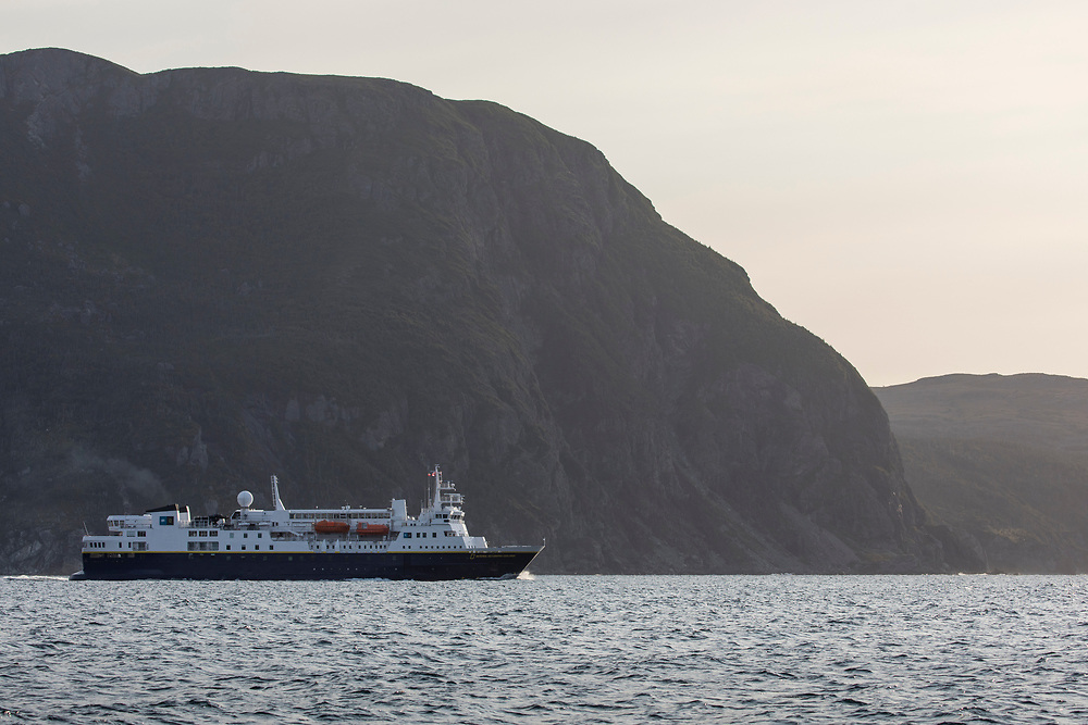 Canada, Newfoundland, Bonne Bay, Cruise Ship National Geographic Explorer steams in Gros Morne National Park on summer afternoon