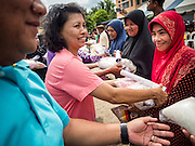 14 JUNE 2015 - NARATHIWAT, NARATHIWAT, THAILAND: Community leaders (left) hand out food staples in Narathiwat. Community leaders hand out food every year before Ramadan, which starts June 18. The annual food distribution event is organized by the Southern Peace Media Club, a group of Thai journalists who work in the southern provinces of Pattani, Narathiwat and Yala. An insurgency pitting Muslim extremists against the Thai government has rocked Thailand's southern three provinces since 2001. More than 6,000 people have been killed in the sectarian violence.    PHOTO BY JACK KURTZ