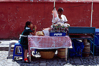 A woman and her daughter sell food and drinks on the streets of Antigua, Guatemala