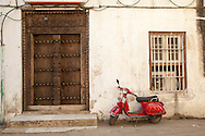 A red motor scooter is parked beside an ornate door in Stone Town, the old part of Zanzibar City, Tanzania