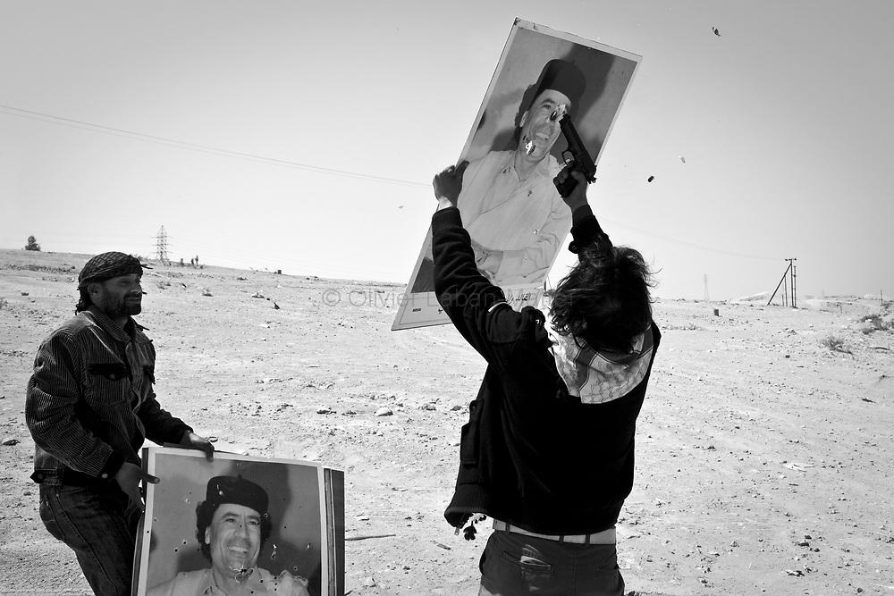 Des combattants rebelles tirent sur des portraits du Colonel Kadhafi, le 27 mars 2011 après avoir libéré la ville de Ben Djaouad.