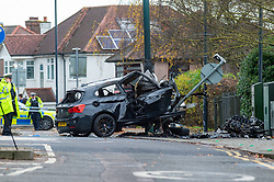 © Licensed to London News Pictures. 07/12/2019. London, UK. Police gather evidence at the scene of a fatal road traffic collision, a black BMW hit a lamp post in the crash, the impact ripped the engine block from the car and it caught fire.<br /> Police were called at 09:08 GMT on Saturday 7th December 2019 to reports of a car in collision with a lamp post on Dollis Hill Lane at the junction with Brook Road, NW2. Metropolitan Police Officers, the London Ambulance Service and London Fire Brigade attended. Two people were recovered from the vehicle. The male driver was pronounced dead at the scene at 09:21 GMT. The passenger has been taken to a central London hospital. Photo credit: Peter Manning/LNP