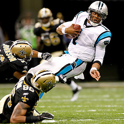 January 1, 2012; New Orleans, LA, USA; Carolina Panthers quarterback Cam Newton (1) is tackled by New Orleans Saints defensive tackle Tom Johnson (96) and linebacker Martez Wilson (95) during the second half of a game at the Mercedes-Benz Superdome. The Saints defeated the Panthers 45-17. Mandatory Credit: Derick E. Hingle-US PRESSWIRE