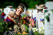 On Memorial Day, Brittany Jacobs of Hertford, North Carolina sits with her son, Christian, at the gravesite of her husband, Marine Sgt. Christopher Jacobs, in National Cemetery in Arlington Virginia, USA on 27 May, 2013.