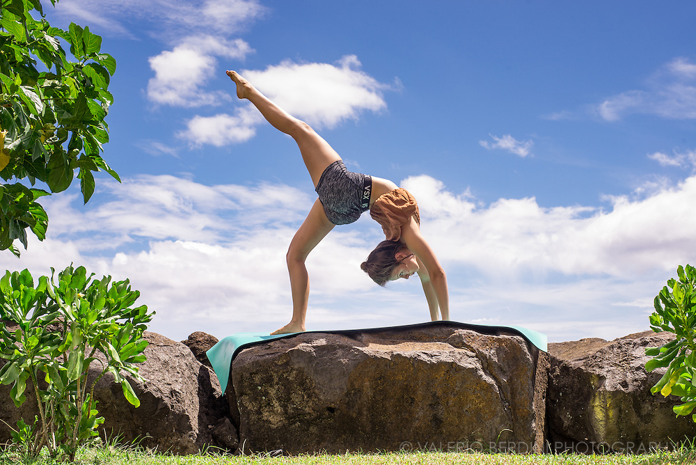 A girl practices yoga positions over a mat laid on a rock in Papeete