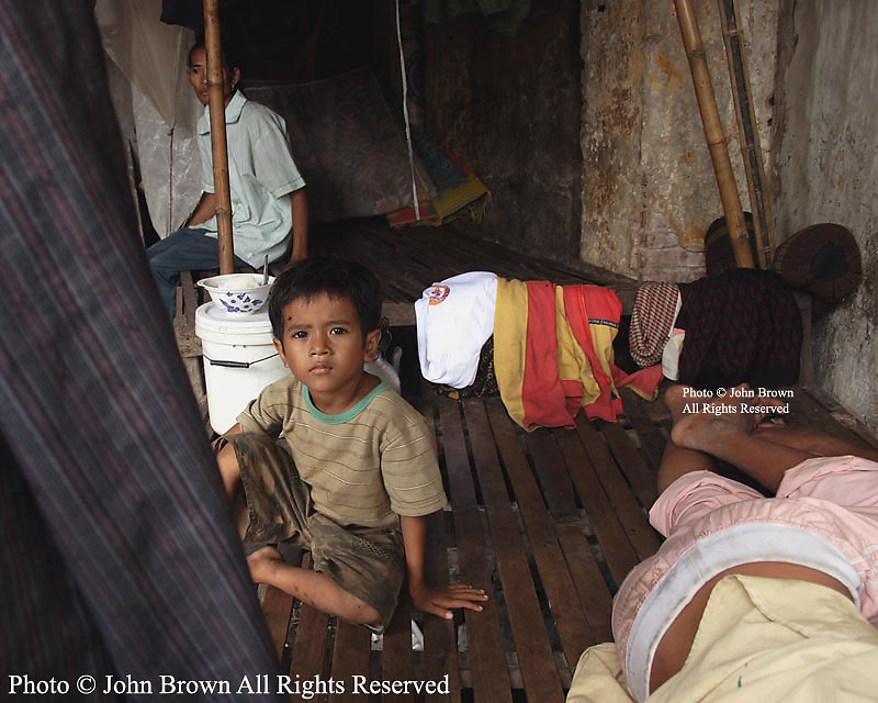 A young boy sits on a wooden bed while another sleeps during Election Day 2008 in Kampong Cham, Cambodia. They are among the 2% of residents living in third world countries that earn their livings collecting recyclable material.