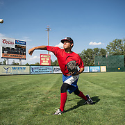 The Vancouver Canadians pitcher, Adaric Kelly, works out his arm by throwing in the outfield before a game vs. the Boise Hawks in Boise, Idaho.
