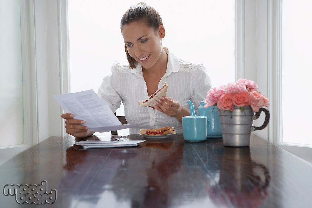 Woman with sandwich reading at dining room table