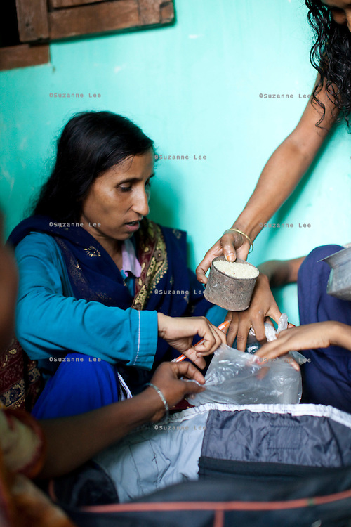 Jesmin Akhter, 26 (in turquoise & blue), barter trades her products with rice in one of her 'marketplaces', Jerai Villlage, Gobindagonj Upazila, Gaibandha, Bangladesh on 19th September 2011. She has found financial independence and contributes to her household income by working as a saleswoman, earning 3500 - 5000 Bangladeshi Taka per month. She is the top saleswoman under her 'hub', out of 30 women. Having worked for about 2.5 years, she cycles from village to village and door to door in a country where women on bicycles is an extremely uncommon sight. She is one of many rural Bangladeshi women trained by NGO CARE Bangladesh as part of their project on empowering women in this traditionally patriarchal society. Named 'Aparajitas', which means 'women who never accept defeat', these women are trained to sell products in their villages and others around them from door-to-door, bringing global products from brands such as BATA, Unilever and GDFL to the most remote of villages, and bringing social and financial empowerment to themselves.  Photo by Suzanne Lee for The Guardian