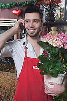 Florist stands on mobile phone with  hydrangea