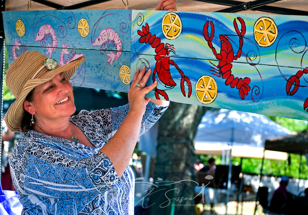 Sue Cox, owner of Funky Yard Art, hangs up one of her whimsical patio plaques during an outdoor art market May 8, 2011 at the Mary C. O'Keefe Cultural Center in Ocean Springs. The market is held on the first Saturday of every month from 10 a.m. to 4 p.m. and showcases the wares of local artisans. (Photo by Carmen K. Sisson/Cloudybright)