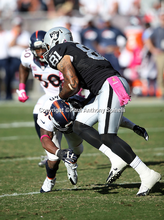 Oakland Raiders tight end Mychal Rivera (81) gets tackled low by Denver Broncos strong safety T.J. Ward (43) as he catches a fourth quarter pass for a gain of 4 yards during the 2015 NFL week 5 regular season football game against the Denver Broncos on Sunday, Oct. 11, 2015 in Oakland, Calif. The Broncos won the game 16-10. (©Paul Anthony Spinelli)