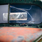 A close-up of an old truck sits by fuel pumps in an abandoned gas station in the ghost town of Bodie, California.