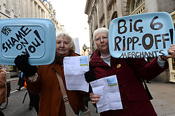 Pictured are sisters Doreen Laws and Linda Ford from Romford in Essex with their energy bills.<br /> UK Uncut and Fuel Poverty Action, anti-austerity groups,  protest at The Royal Exchange and Threadneedle Street at the NPower offices against rises in domestic fuel bills. London, UK, Tuesday, 26th November 2013. Picture by Ben Stevens / i-Images