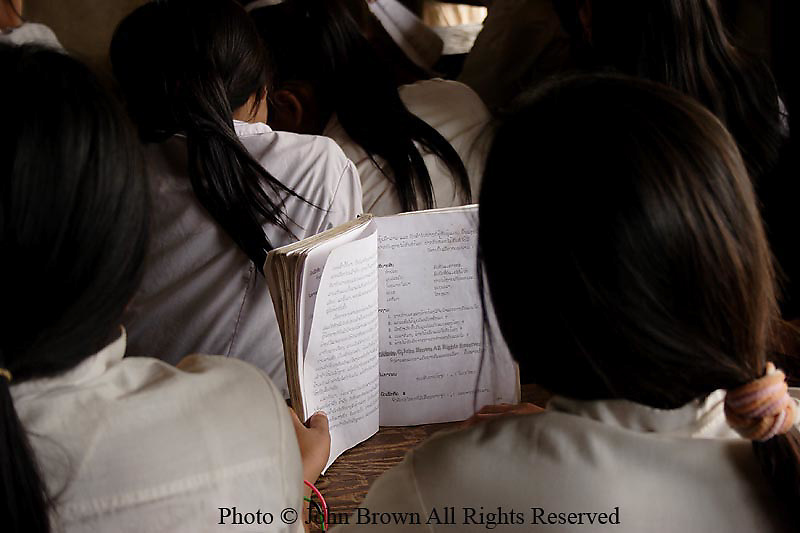 A student reads a Lao language book in cramped conditions at The Ban Buamlao Primary School in Ban Buamlao, Laos.