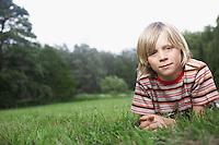 Portrait of boy (7-9) lying in meadow