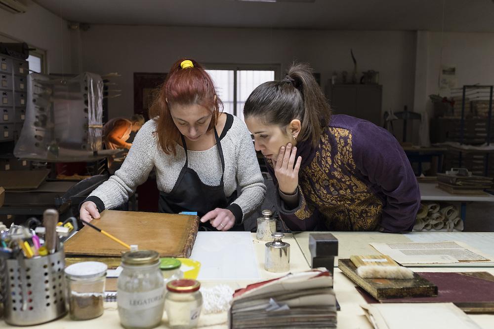 Carola Gottscher e una studentessa dell'universit&agrave; di Tor Vergata di Roma mentre studiano la scelta del tipo d'intervento per restaurare una legatura in vitello<br /> ancient binding on calf cover