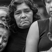 "Both Imelda Mendez (center) and her daughter, Roxana de Peréz, comfort their children at the burial of Nelson Omar Chilel Lopez in El Porvenir. ""He was a humble, obedient boy,"" says Mendez, who along with de Peréz, cared for the child when his family migrated north."