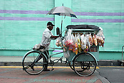 A man is walking on a city street selling snack food from a wheeled cart in Georgetown, Penang, Malaysia.