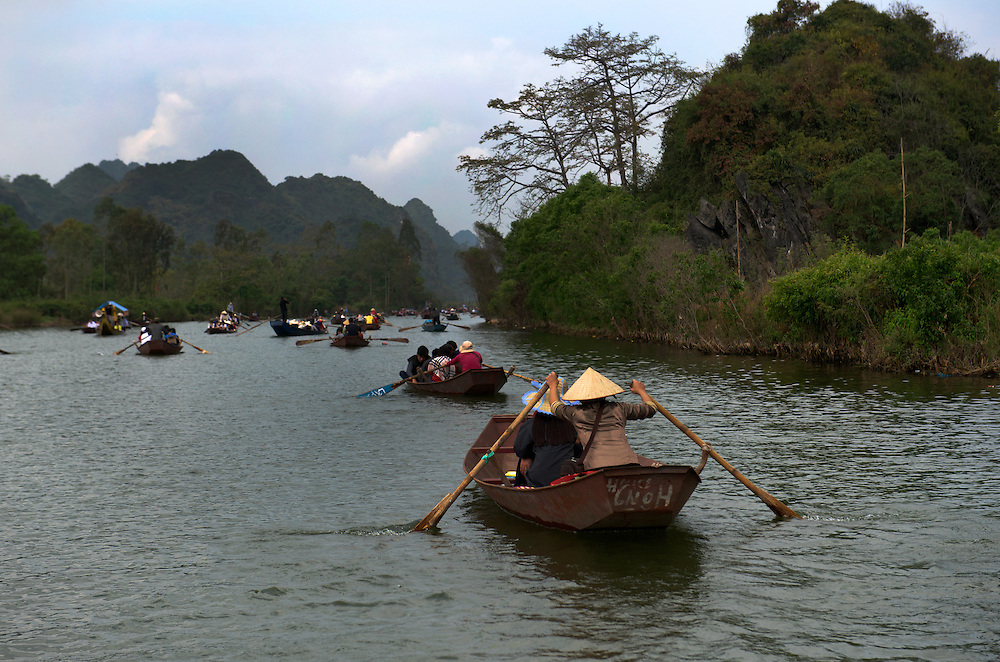Pilgrims travel by rowing boat along the Yen River to the Perfume Pagoda, the most important Buddhist pilgrim site in Vietnam.