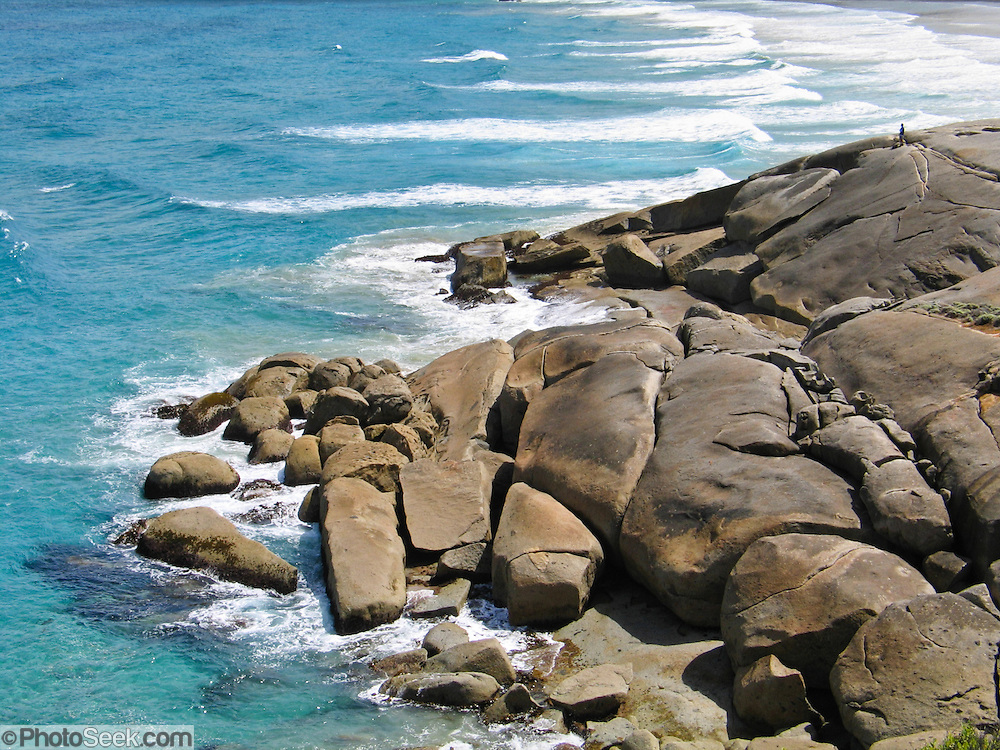 """Indian Ocean (or Southern Ocean according to Australian geographers) waves wash onto granite shoreline at Wilson's Promontory National Park in the Gippsland region of Victoria, Australia. Drive two hours from Melbourne to reach Wilson's Promontory, or """"the Prom,"""" which offers natural estuaries, cool fern gullies, magnificent and secluded coastal beaches, striking rock formations, and abundant wildlife."""