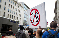 © Licensed to London News Pictures. 11/06/2013. London, UK. A protester brandishes an anti-G8 sign on Lower Regent Street during anti-capitalist protests in London today (11/06/2013). The small demonstration, part of an organised anti-capitalist protest in central London, was timed to coincide with the G8 meeting of world leaders in Northern Ireland this week. Photo credit: Matt Cetti-Roberts/LNP