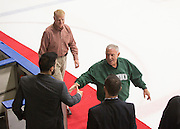 Elmer Gates shakes hands with hockey Assistant Coach Nathan De La Torre as he walks onto the ice with other 1960s hockey alumni after the first period of the OU vs. Kent State hockey game on September 30, 2016.