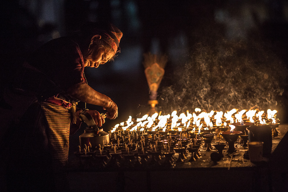 An old Tibetan woman in the street of Kathmandu, Nepal, lights butter candles to celebrate Losar, the Tibetan new year. In Buddhism, the lights of the candles represent the illumination of wisdom against the darkness of ignorance.