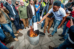 Pictured: Protesters burn their eviction letters from private firm SERCO.<br /> <br /> Protesters gathered outside the main Home Office building in Glasgow to protest at private company SERCO's attempts to evict failed asylum seekers from their homes.<br /> <br /> &copy; Dave Johnston / EEm