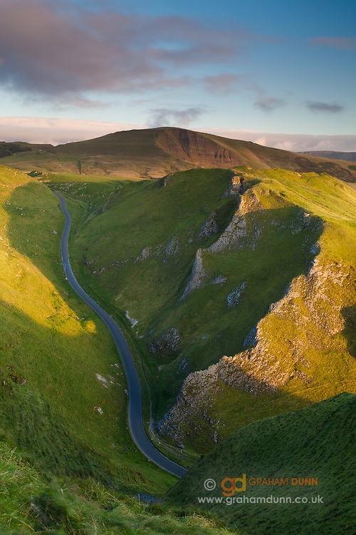 The road winds its way through Winnats Pass and its impressive limestone walls. Mam Tor is seen on the horizon. Peak District.
