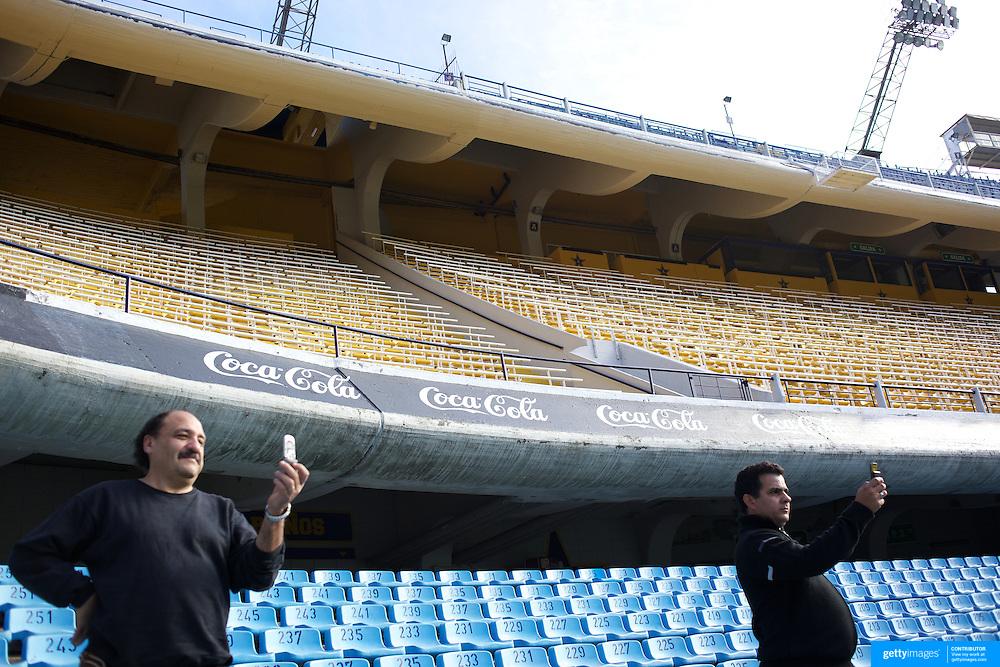 Men take photographs while on a tour of the famous Boca Juniors football stadium, La Bombonera, in La Boca region of Buenos Aires, Argentina, 25th June 2010. Photo Tim Clayton...