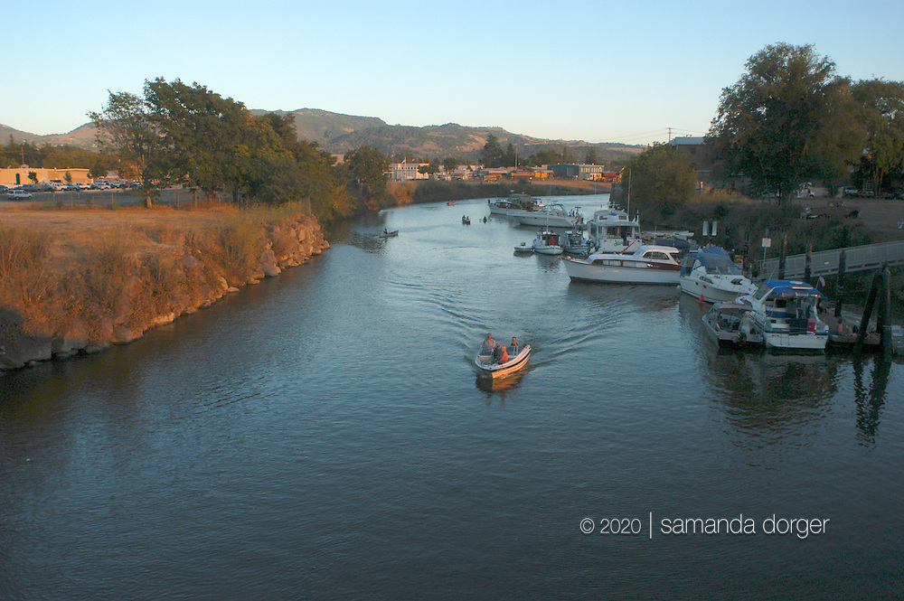 A boat travels upstream in the Napa River, in Napa, California, USA.