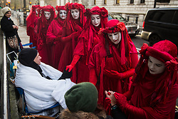 London, UK. 29 November, 2019. Members of Extinction Rebellion's Red Rebel Brigade show support to hunger striking Extinction Rebellion climate activists outside the Liberal Democrat headquarters on the twelfth day of an 'Election Rebellion' hunger strike with three demands for election candidates: to tell the truth by declaring a Climate and Ecological Emergency, to promote policies to halt biodiversity loss and reduce greenhouse gas emissions to net zero by 2025 and to help the Government create and be led by a Citizen's Assembly on climate and ecological justice.