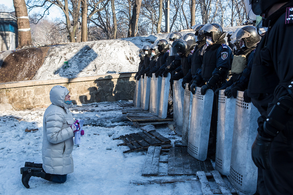KIEV, UKRAINE - JANUARY 24: A woman prays on her knees in front of a line of police officers on the street near the Cabinet of Ministers building and Dynamo stadium, site of recent clashes, on January 24, 2014 in Kiev, Ukraine. After two months of primarily peaceful anti-government protests in the city center, new laws meant to end the protest movement have sparked violent clashes in recent days. (Photo by Brendan Hoffman/Getty Images) *** Local Caption ***
